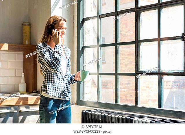 Young woman entrepreneur standing in company kitchen, talking on the phone
