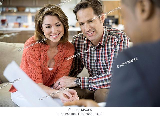 Couple talking to financial advisor in living room