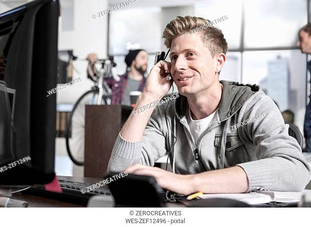 Young man at desk in office wearing a headset