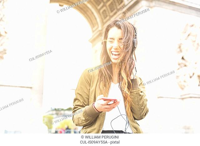 Young woman laughing while listening to headphones at Arc de Triomphe, Paris, France