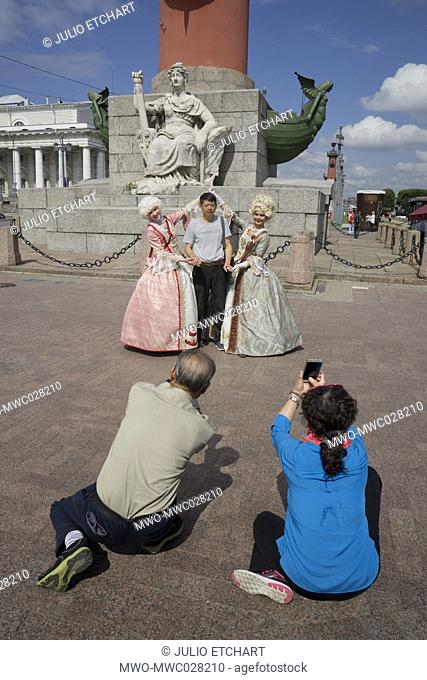 Chinese tourists taking pictures of local Russian guides in period dress by the Neva river, St.Petersburg,Russia