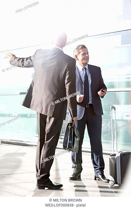 Two businessmen outside airport building