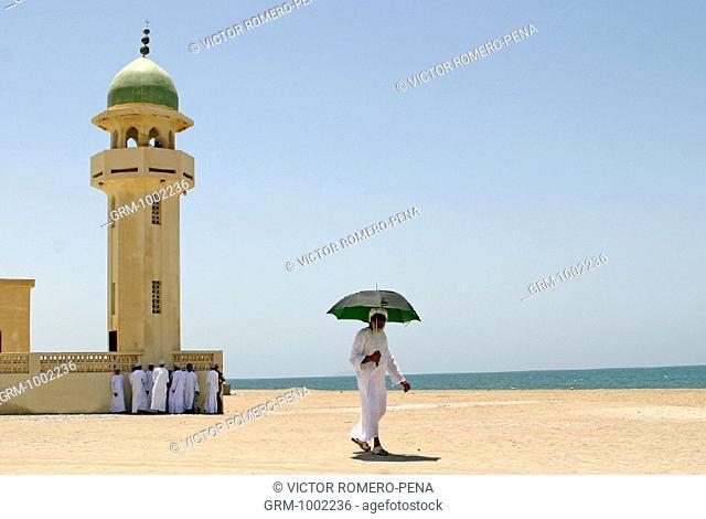 Omani man with umbrella at a mosque in Barka, Oman