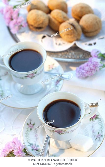 Two cups of black coffee and macaroon on back