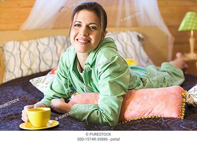 Woman lying on bed and holding cup of tea