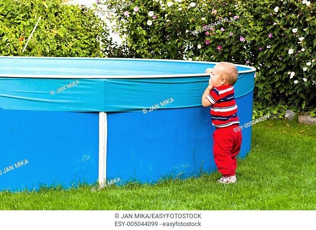 Toddler boy exploring swimming pool in the garden