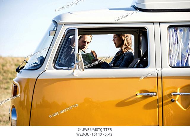 Couple on a road trip in their camper, looking at map