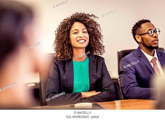 Over shoulder view of young businesswoman at boardroom meeting