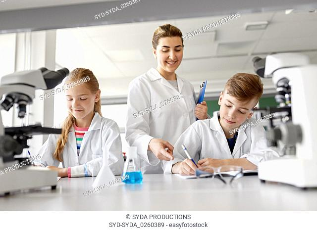 teacher and students studying chemistry at school
