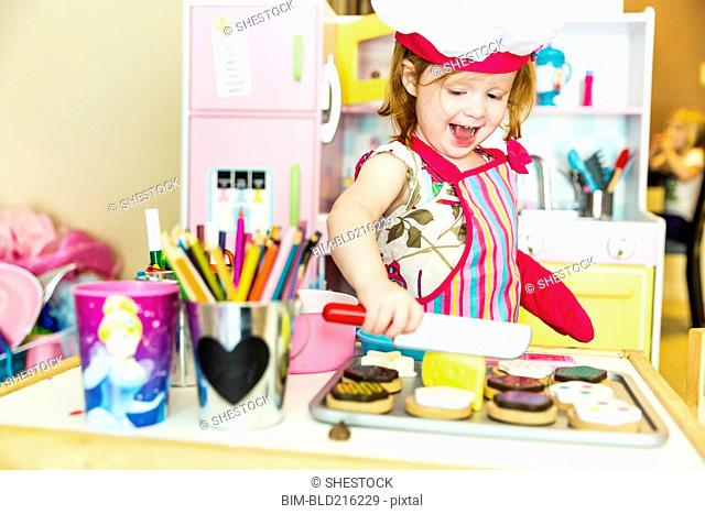 Caucasian girl playing with toy kitchen