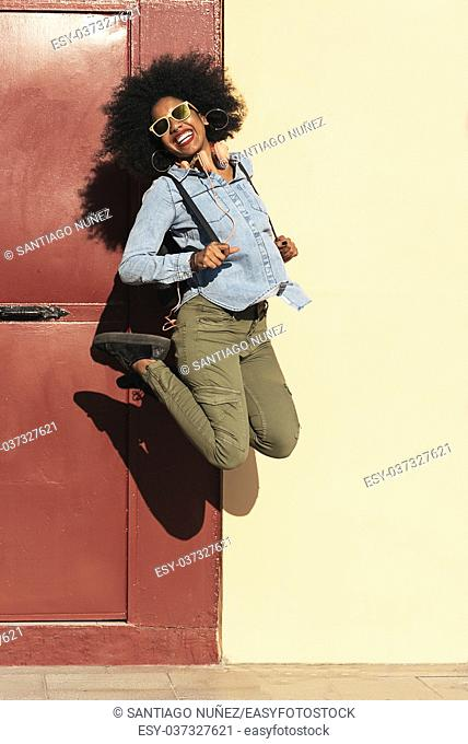 Portrait of beautiful afro american woman jumping in the street