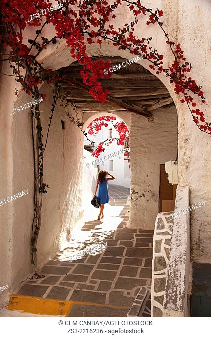 Woman walking through an archway in town center Chora, Ios, Cyclades Islands, Greek Islands, Greece, Europe
