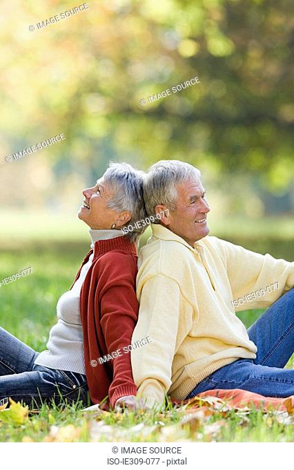 Senior couple sitting back to back in a park