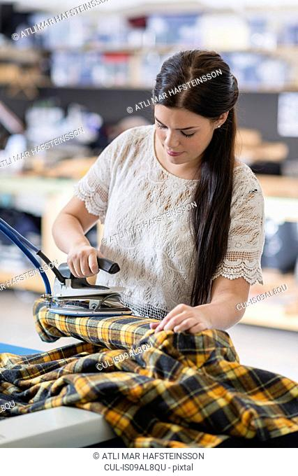 Young seamstress ironing tartan jacket in workshop
