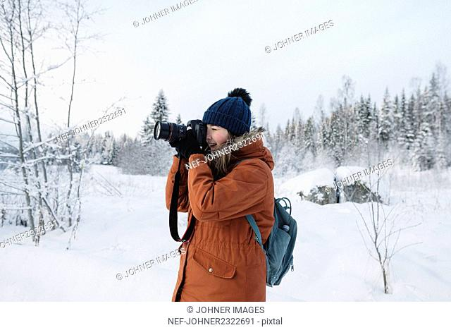 Young woman with camera hiking in winter