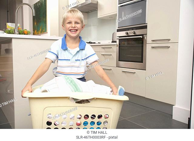 Boy carrying basket of laundry
