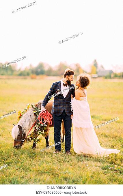 Happy wedding couple walking the little pony on the field