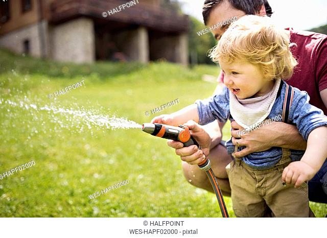 Little boy with his father watering the lawn