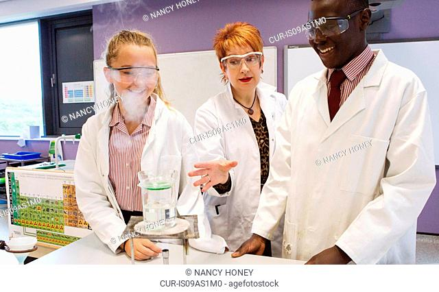 Students and teacher working in chemistry lab