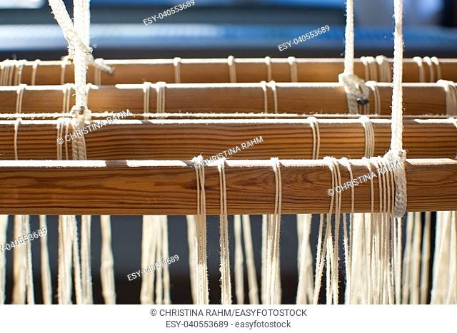 Closeup of loom threads and wood pins in sunlight