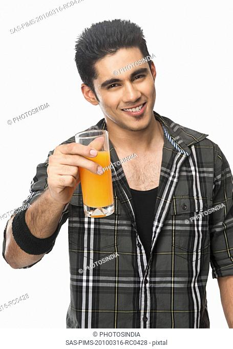 Man holding a glass of juice and smiling