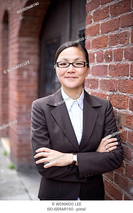 Businesswoman with arms crossed next to brick wall