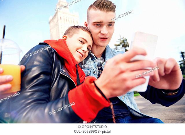 Young couple taking smartphone selfie in city