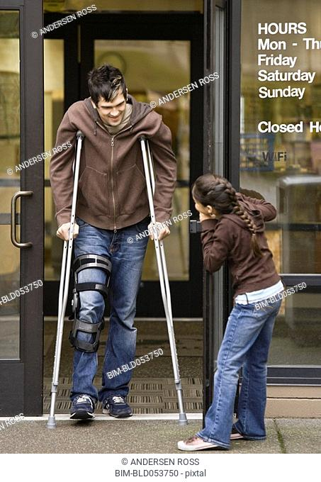 Mixed Race girl holding door for man on crutches