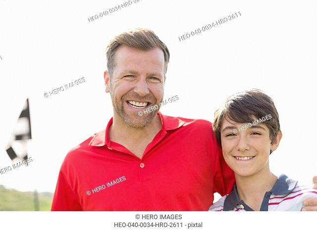 portrait of father and pre-teen son on golf course