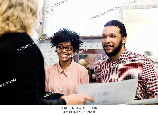 Businesswoman talking to young couple