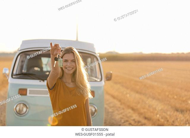 Happy young woman holding car key at camper van in rural landscape