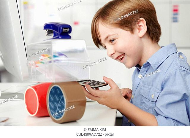 Boy playing with office equipment