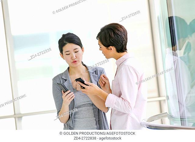 Two Businesswomen using smartphone