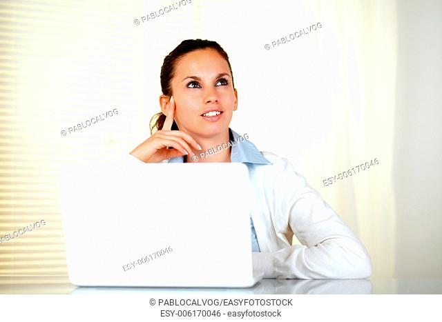 Pensive caucasian young woman looking up in front of her laptop - copyspace