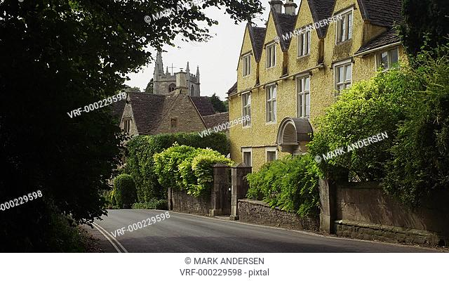 Medium shot of road and large residential house in town / Castle Combe, England, United Kingdom
