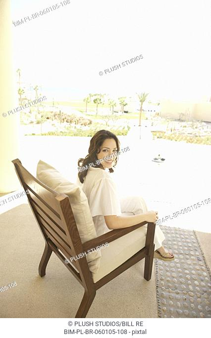 Woman sitting in wooden deck chair at hotel, Los Cabos, Mexico