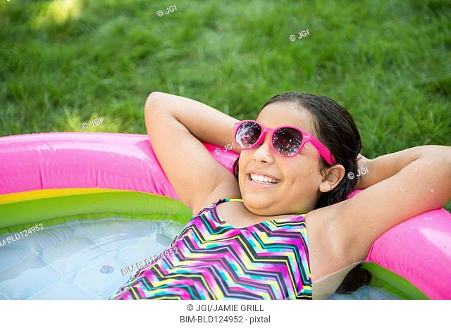 Mixed race girl relaxing in wading pool