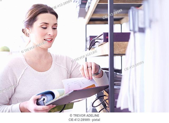 Interior designer browsing fabric swatches in office