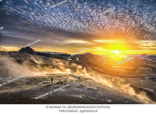 Woman standing by geothermal hot springs, mud pots and fumaroles, Namaskard close to Lake Myvatn, Northern, Iceland