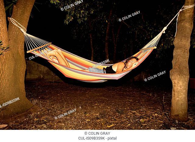 Young woman asleep in hammock at night