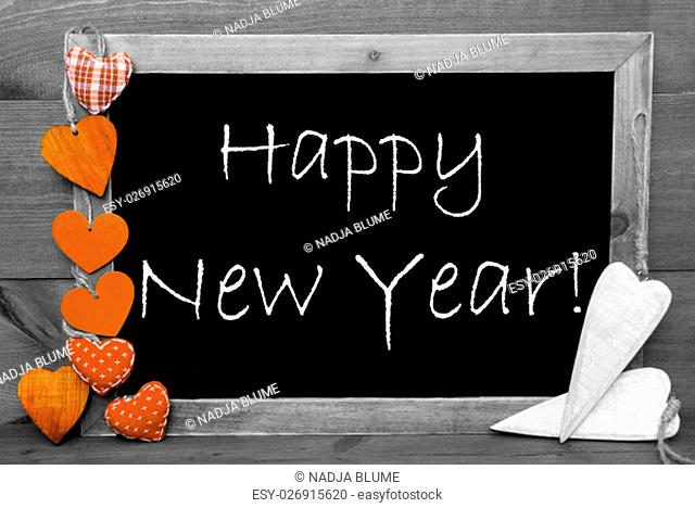 Chalkboard With English Text Happy New Year. Orange Hearts. Wooden Background With Vintage, Rustic Or Retro Style. Black And White Image With Colored Hot Spots