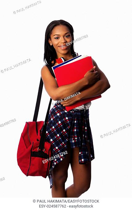 Beautiful happy student standing with binders, books, notepads and bag, on white