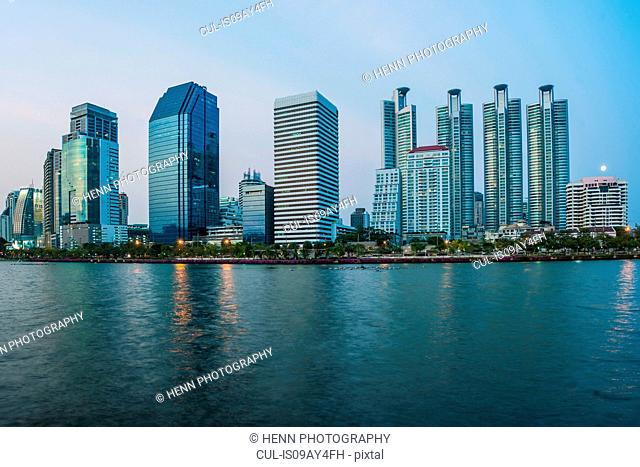 View across river of skyscrapers on skyline, Benjakiti Park, Bangkok, Thailand