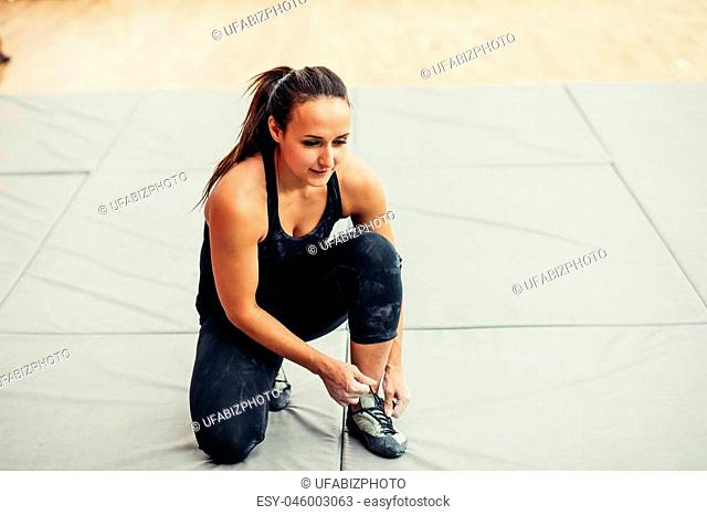 Sporty woman binding the laces on shoes at climbing gym before exercise