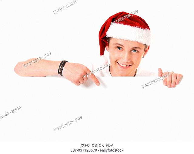 Young Santa Claus pointing in white blank sign with smile, isolated on white background