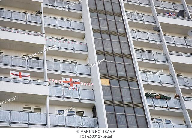High rise apartment building adorned with English flags, London, England