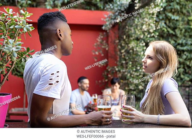 Young couple talking having a beer at outdoor bar