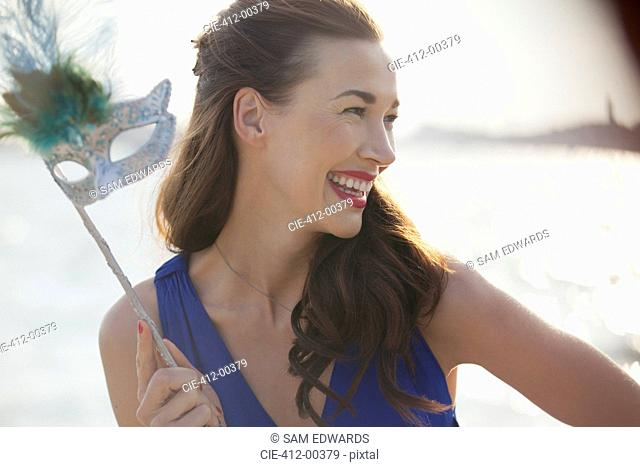 Close up of smiling woman holding mask