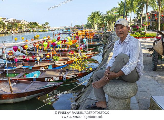 Local Vietnamese fisherman sitting on a capstan at the side of the harbour on Son Thu Bon river, Hoi An, Quang Nam Provence, Vietnam, Asia