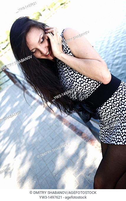 Sexy 25 year old pretty woman outdoors talking by cell phone